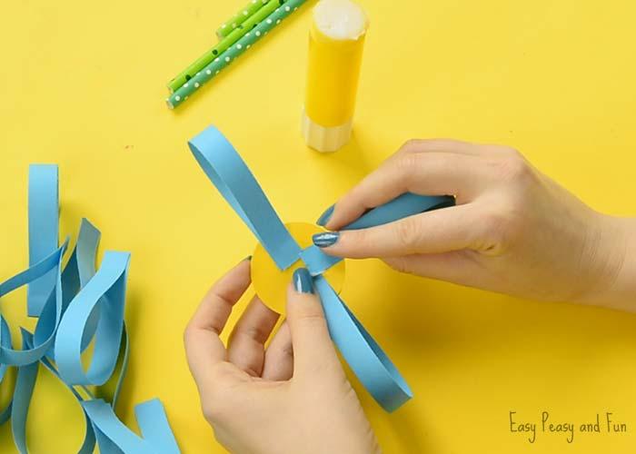 Paso 4 - Pegamos las tiras de papel al circulo de cartulina amarilla